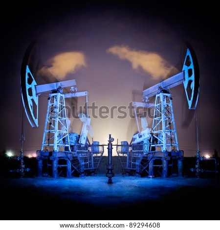 Two oil pumps jack in action. Night view. Long exposure.