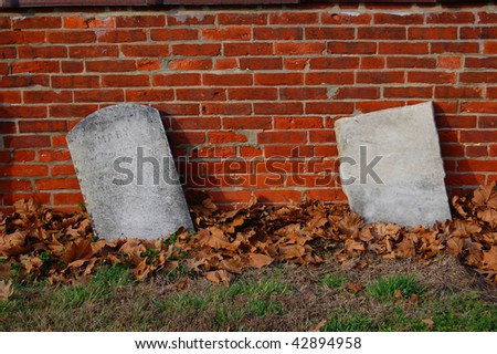 Two old, abandoned headstones propped up against a brick wall