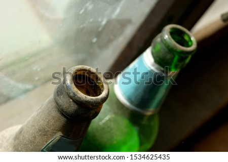 two old beer bottles forgotten on the windowsill in the attic