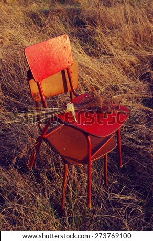 Two old chairs and bouquet from dry flowers and herbs in a dry grass in the open air in evening beams of the sun. Old furniture