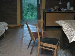 two old chairs and open door, abandoned house interior, concept of desolation and decay