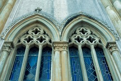 Two old church windows in medieval Gothic style with stained glass.