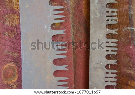 Two old crosscut saw blades look ornate in their design when photographed close up.