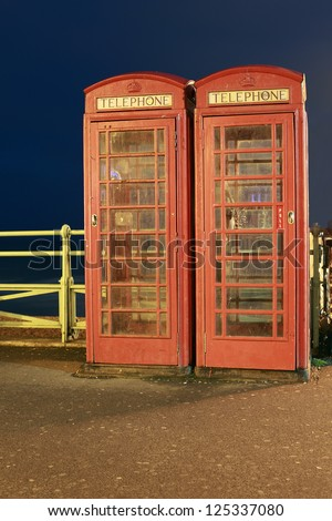 Two old-fashioned telephone boxes along the seashore in Brighton, England.