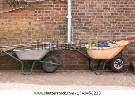Two Old Garden Carts with Garden Tools and Green Plant are Near Brick Wall. Trolleys gardener. Concept: Gardening and Agriculture.