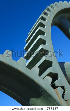 Two old interlocking gear wheels,  slightly rust-streaked, from some abandoned piece of machinery, set against a clear blue sky. Space for text.