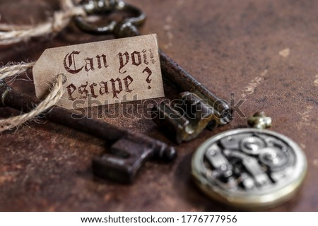 two old keys on a rusty metal table with labels : can you escape ? Stock photo ©