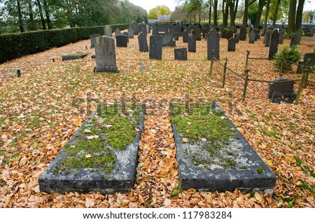 Two old lying gravestones on a graveyard in the autumn - stock photo