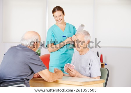 Two old men playing cards in a nursing home with smiling nurse watching