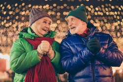 Two old people white grey hair woman man enjoy x-mas christmas tradition fair discounts hold fists gloves under newyear lights outdoors wear coat headwear scarf