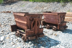 two old rusty minecarts on a background of stones