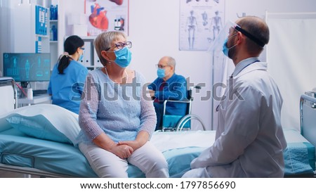 Two old senior persons at doctor wearing masks and talking with nurse and doctor in protective wear. Modern private clinic or hospital ward during COVID 19 pandemic. Healthcare medicine appointment