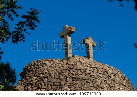 Two old ston crosses in Barcelona over blue sky
