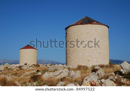 Two old stone windmills on the hills above Emborio on the Greek island of Halki.