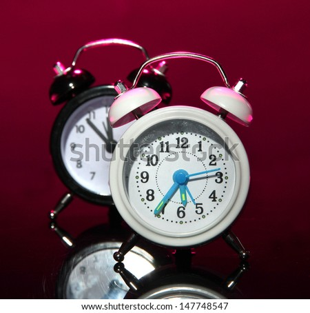 Two old style alarm clocks on dark color background