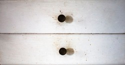 Two old white grunge scratched drawers with old rusty knobs
