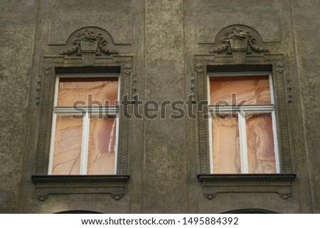 Two old windows in white orange color with a decorative stone reliefs, on a brown grey facade. Vienna facade detail #1495884392