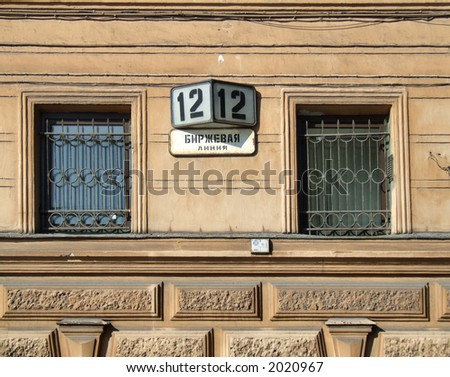 Two old windows, street number and the street name written Cyrillic alphabet (Russian city).