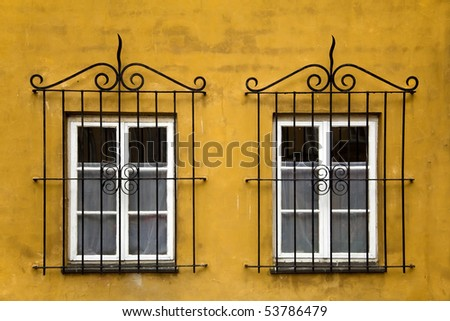 Two old windows with ornamented metal lattice