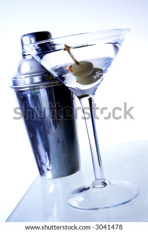 Two olive martini on underlit bar with shaker