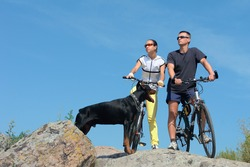 Two on bicycles and black dog against blue sky