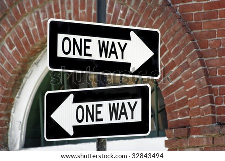 Two one-way signs showing two different directions