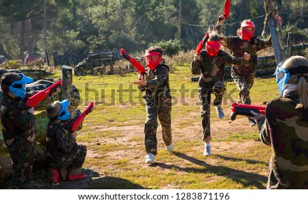 Two opposing teams of nice kids shooting on paintball playing field outdoors