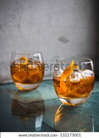Two orange campari cocktails ( Old-Fashioned / Negroni / Aperol Spritz) with ice on a contrast turquoise background, vertical, side view. Light through the liquid