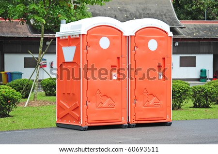 Two Orange Color Portable Toilet In The Park