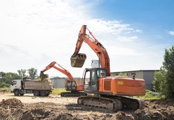 two orange crawler excavators and a gray dump truck in the process of excavation. Site preparation. Loading and transportation of soil