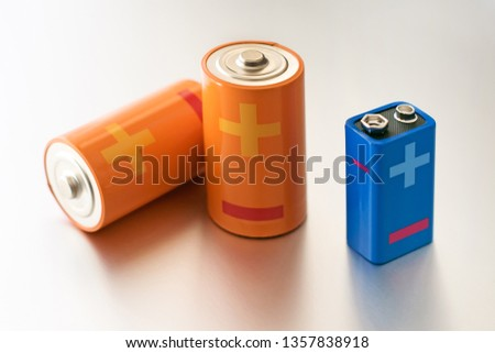 Two orange D size batteries and one 9V blue battery with big plus and minus polarity symbols.On silver background, viewed from high angle #1357838918