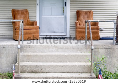 Two orange lounge chairs on the front porch of an   American home.