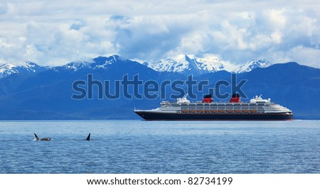 Two orca whales     and cruise  liner are shown on snow mountains   background, Alaska, the USA