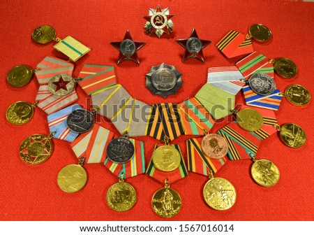 """Two orders of the """"red Star"""" with the inscriptions """"USSR"""" and """"Proletarians of all countries unite"""", the order of the """"Patriotic war"""", the order of China and a group of medals of the USSR."""