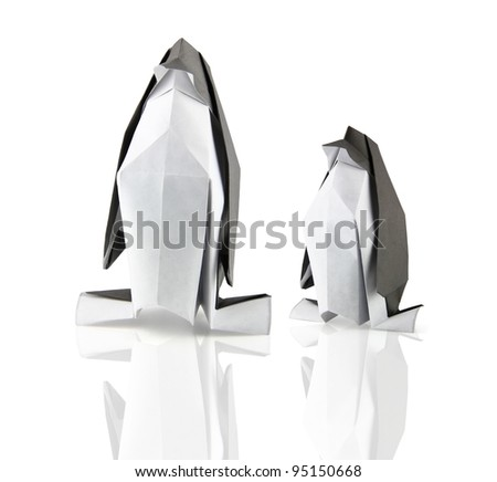 two origami penguins on the white reflection background