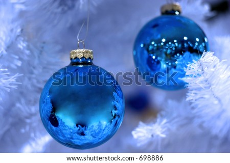 two ornaments on frosted christmas tree