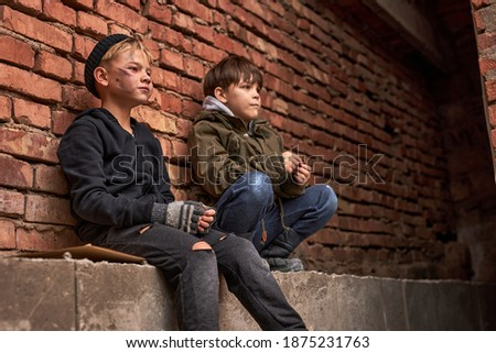 two orphans children begging in town streets, it's cold outdoors, need shelter and monety to survive Zdjęcia stock ©