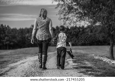 Two Out of Three: A mother and son walk together hand in hand. The little boy holds the hat of his father, who was killed in the line of duty.