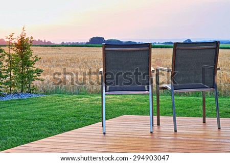 Two outdoor chairs on a wooden veranda, in front of a field and the sunset.