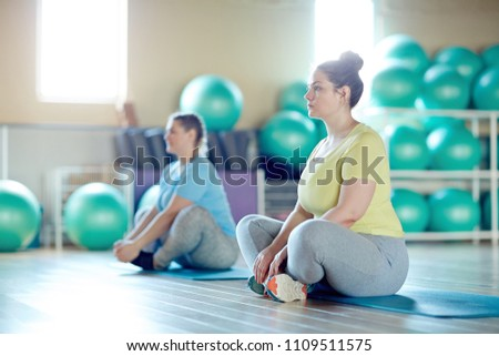 Two overweight women sitting with crossed legs on mats and getting ready for next exercise