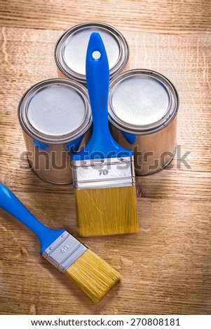 two paint brushes and three cans on wooden board construction concept