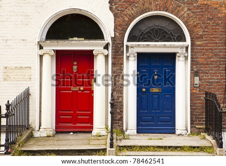 Two painted doors in Dublin stand side by side providing a colorful view. With a red and blue door complimented by traditional and whitewashed brick walls, the contrast is interesting.