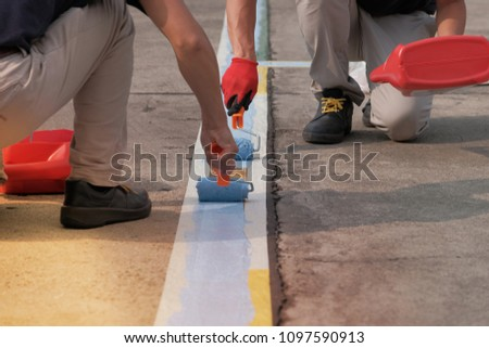 Two painters painting parking lots blue lines striping in a car park.  #1097590913