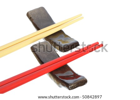 Two pair of colored chopsticks lying on rests. Isolated on white with clipping path