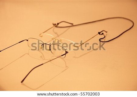 two pair of eye glasses with reflection on sepia background - stock photo