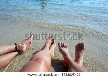 Two pair of legs of young women and one pair of legs of a man rest and relaxed at the beach. women wear anklets. Vacation summer time concept for people relaxing. Sand and sea in background.