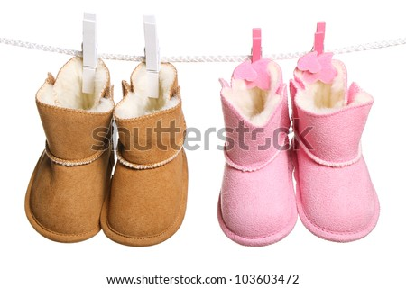 Two pair of winter boots hanging on the clothesline. Image isolated on white background