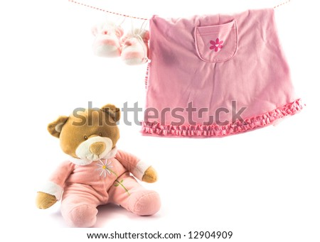 Two pairs of baby's slippers and teddy bear. Copy space