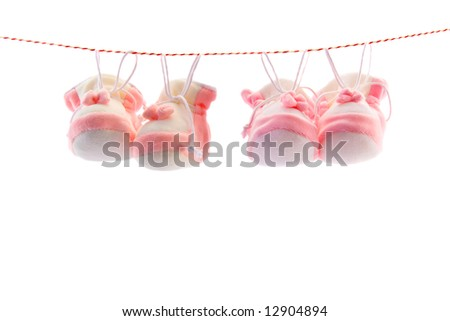 Two pairs of baby's slippers hanging on a rope. Including copy space.
