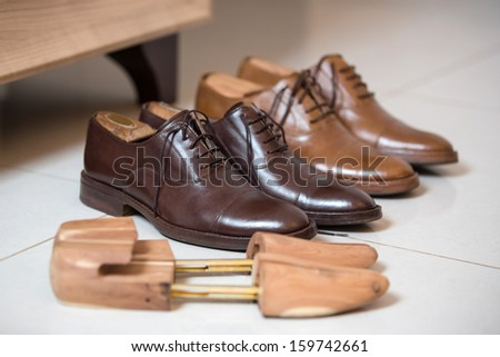 Two pairs of brown handmade classic men\'s shoes  with a shoe pads and stretchers inside and beside the shoes